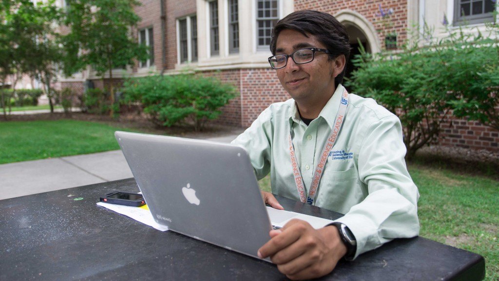Student in green shirt using a laptop on campus